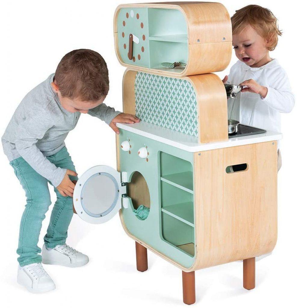La cuisine en bois jouet Janod possède une machine à laver.