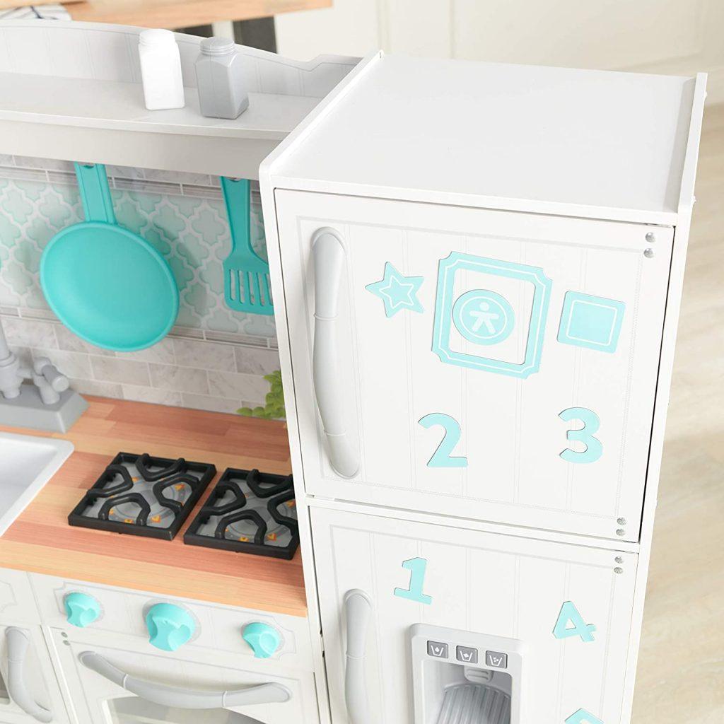 La cuisine Kidkraft Countryside en bois inclut des aimants à mettre sur le réfrigérateur et le congélateur.