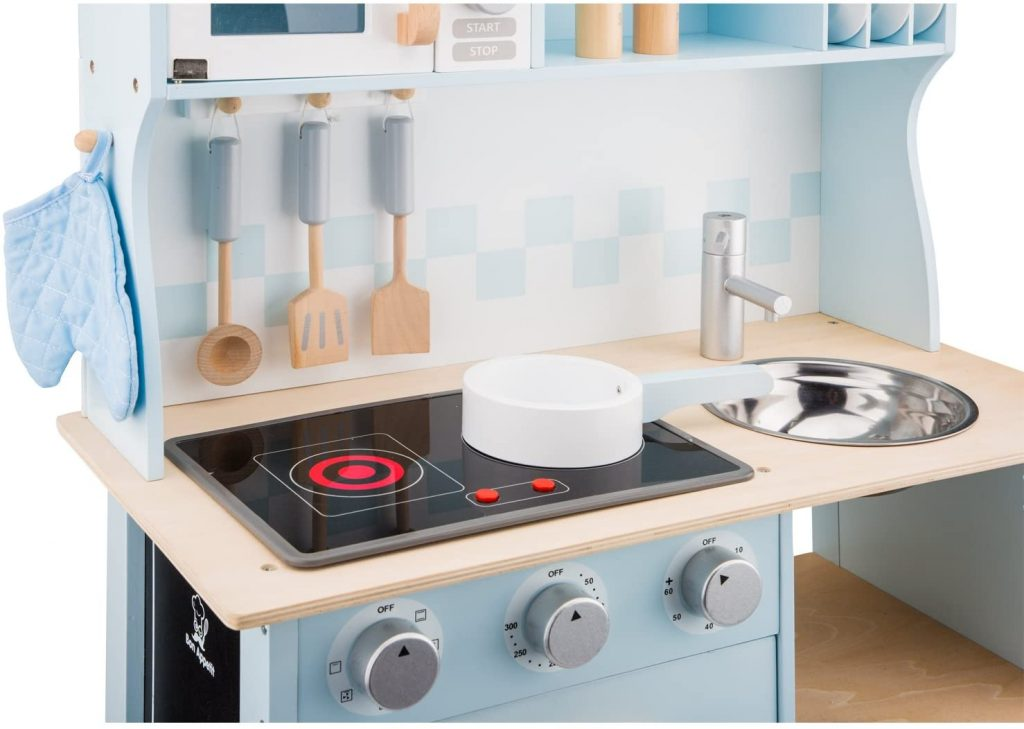 Cette cuisine enfant New Classic Toys a une plaque de cuisson lumineuse et sonore.